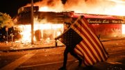 A man is carrying America Flag on fire