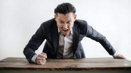 A man wearing black suit is screaming