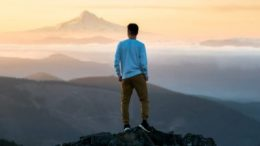 A young man standing on a hill looking at sky